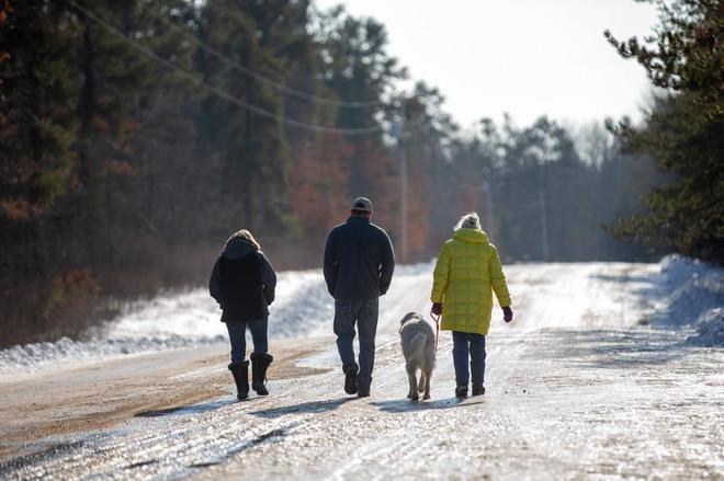 Jeanne Nutter, de amarillo y con su perro, camina por la carretera de Gordon (Wisconsin) donde encontró a Jayme Closs.