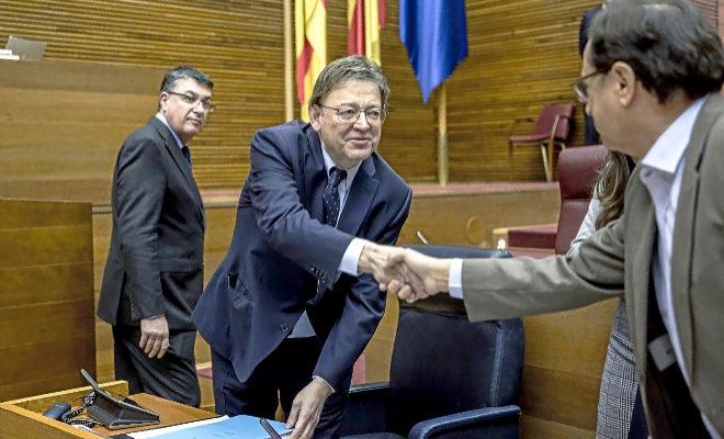 El presidente de la Generalitat,Ximo Puig, saluda al conseller de Hacienda en presencia del presidente de las Cortes Valencianas.