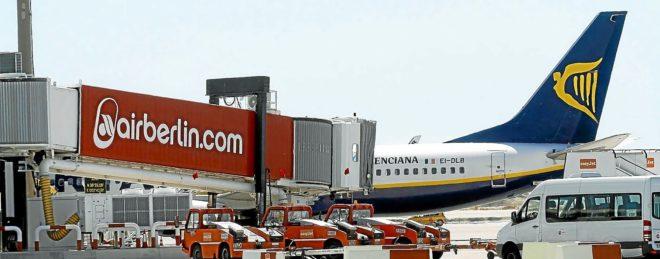 Un avión de Ryanair estacionado en el aeropuerto de Palma junto a un 'finger' con la publicidad de Air Berlin.