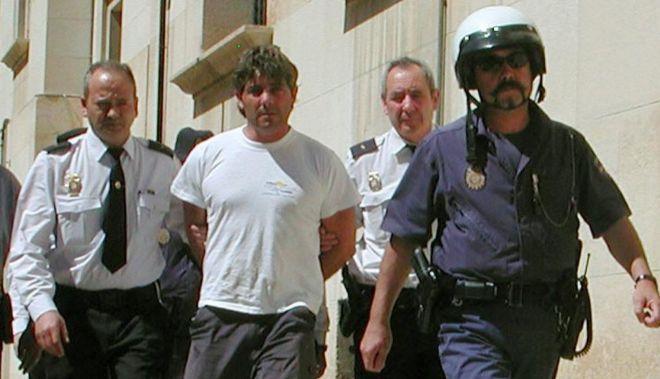 Agentes de la Policía Nacional llevan detenido en 2003 a José Javier Salvador Calvo tras asesinar a su esposa, Patricia Maurel Conte.