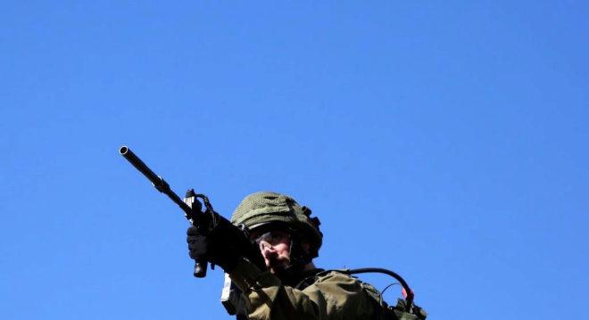 Un soldado israelí mira a través de la mira telescópica de su rifle.