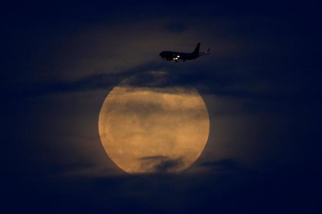 Un avión atraviesa el cielo durante el eclipse lunar.