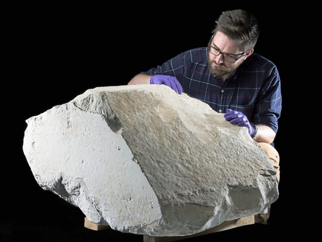 El conservador Daniel Potter con el fragmento de la pirámide.