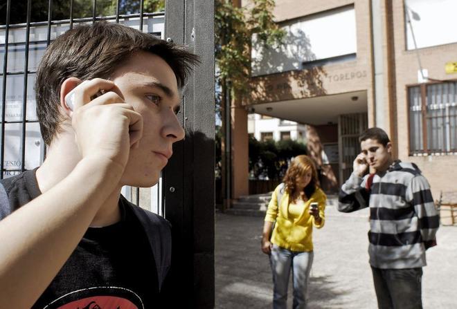 Alumnos hablan con el móvil a la puerta de un instituto de Madrid.