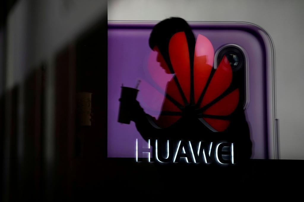 Un hombre camina delante de un anuncia del teléfono Huawei P20.
