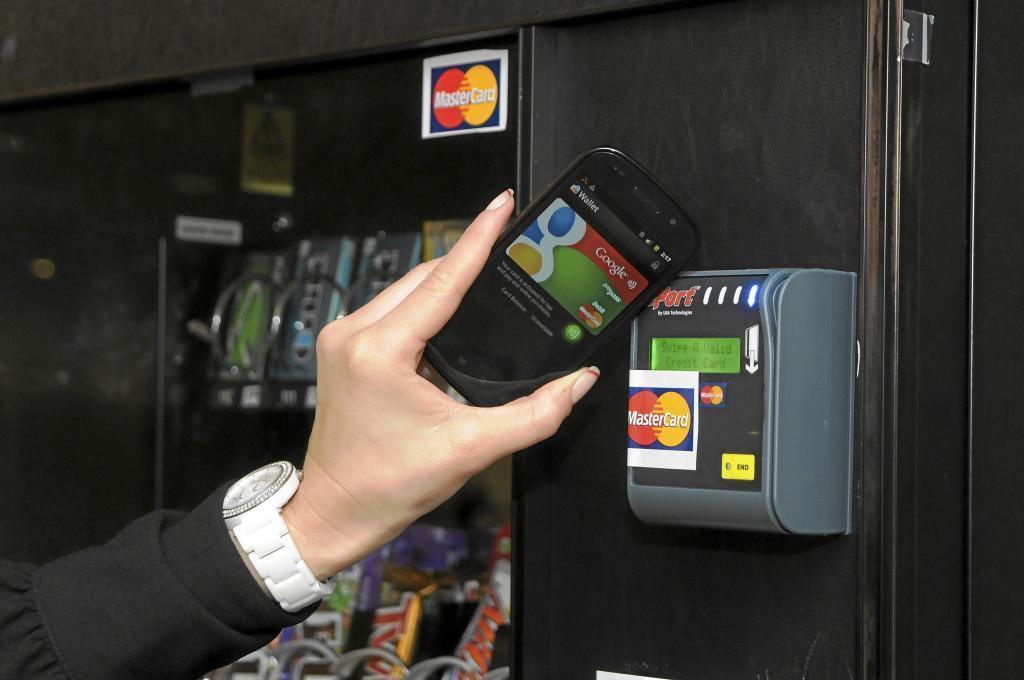 Un smartphone junto a una terminal digital de Mastercard.