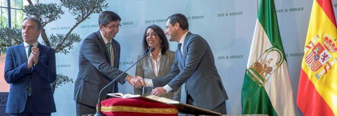Juanma Moreno y Juan María se saludan, en presencia de Marta Bosquet, durante la toma de posesión del nuevo Gobierno de la Junta de Andalucía