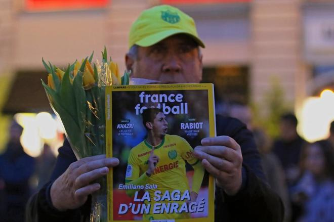 Un hombre muestra la portada de France Football con la foto de Emiliano Sala.