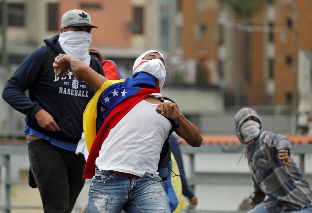 Un manifestante lanza una piedra durante la protesta ayer contra el Gobierno de Maduro en Caracas.