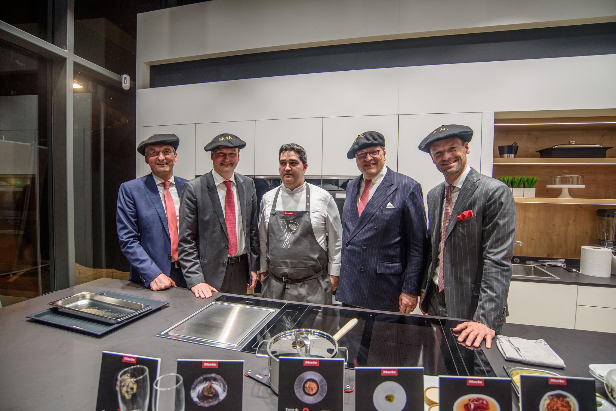Los responsables de Miele ataviados con txapelas junto al cocinero Sergio Ortiz de Zárate.