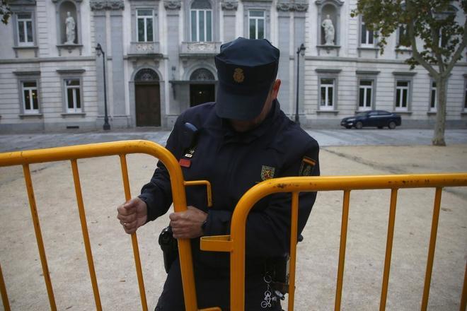 Un policía coloca unas vallas delante del Tribunal Supremo.