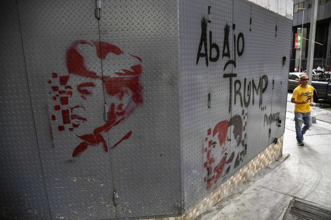 """Un hombre camina junto a un graffitti que dibuja a Chávez y Maduro y el lema: """"Abajo Trump"""", en Caracas."""