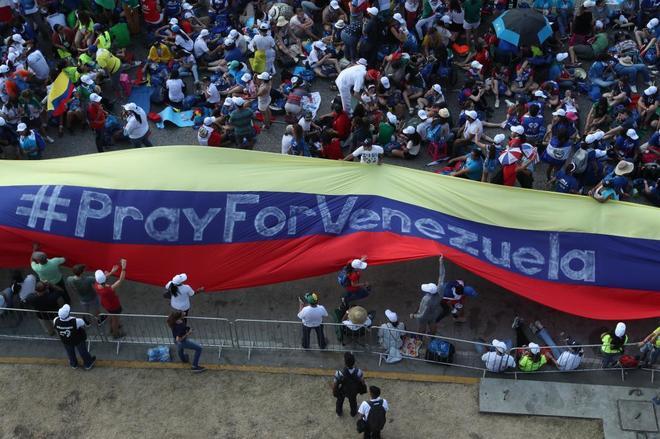 """Peregrinos sostienen una bandera de Venezuela en la que se lee """"#PrayForVenezuela"""" en Ciudad de Panamá."""