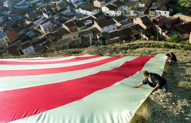 Despliegue de una 'senyera' gigante en la Penya del Sagrat Cor, en el municipio de Alguaire, para celebrar la Diada del año 2003.