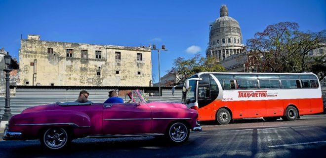Un viejo coche americano usado como taxi y un autobús circulando por las calles de la Habana.