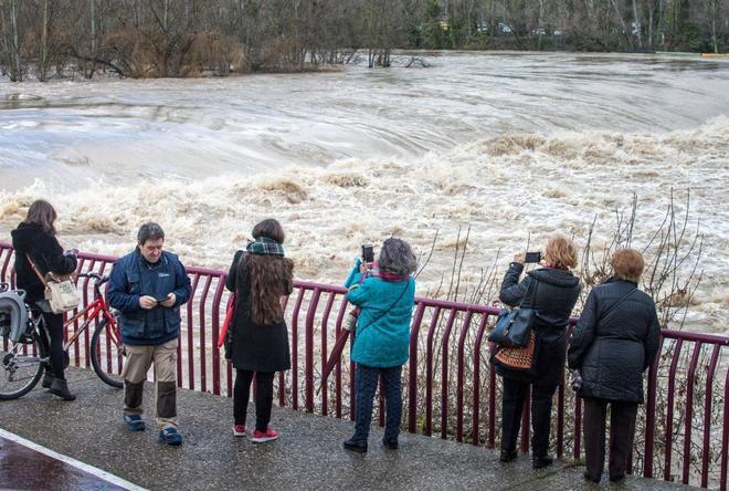 Un  grupo de mujeres hace fotos a la crecida del río Ebro en Logroño