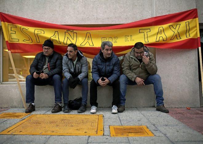 Un grupo de taxistas ante una bandera de España, en Ifema, durante la huelga de esta semana