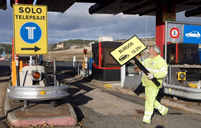 Un operario retirando la señalización del peaje de la autopista AP-1.