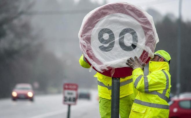 Operarios colocando una de las nuevas señales de 90 km/h.