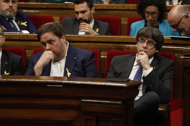 Oriol Junqueras (izda) y Carles Puigdemont en el Parlament de Catalunya durante el anuncio de la Declaración Unilateral de Independencia, en octubre de 2017.