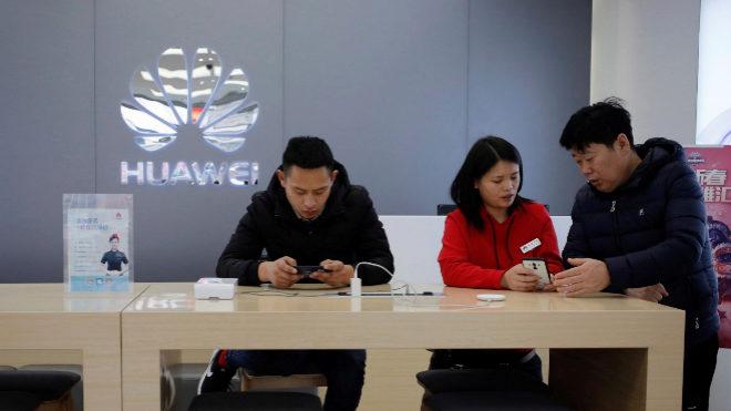 Una vendedora atiende a un cliente en una tienda DE Huawei en Pekín (China)