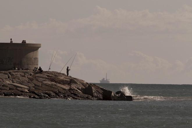 Unos pescadores en la costa de Castellón, con el almacén de gas Castor al fondo.