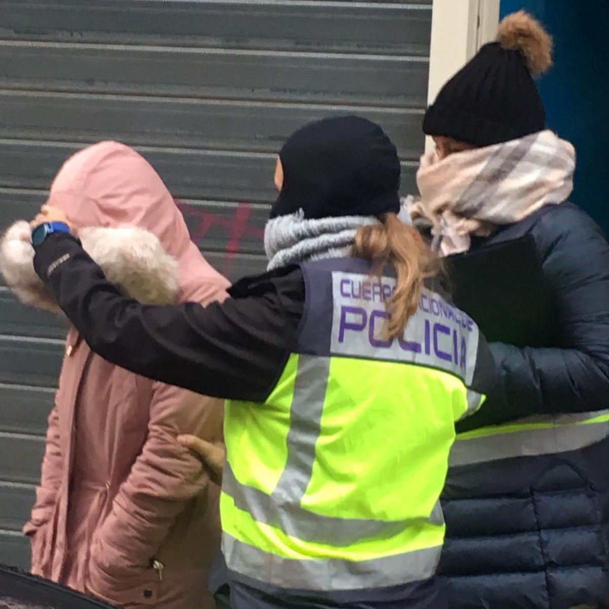Una policía con dos de las detenidas en la operación.