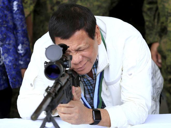 El presidente de Filipinas, Rodrigo Duterte, mira a través de un rifle durante una maniobra militar.