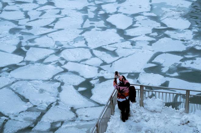 Un hombre hace una foto del río congelado en Chicago.