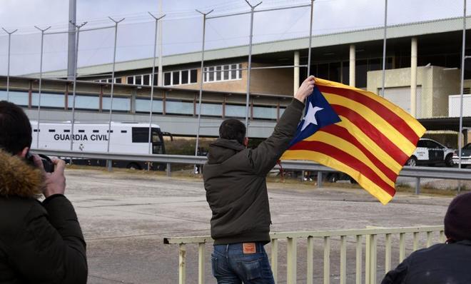 Un hombre ondea una bandera independentista a la llegada de los presos...