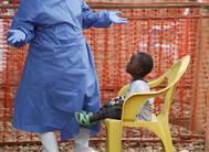 Un trabajador sanitario juega con un niño enfermo de ébola en el centro de tratamiento de la ciudad de Beni, en el Congo.