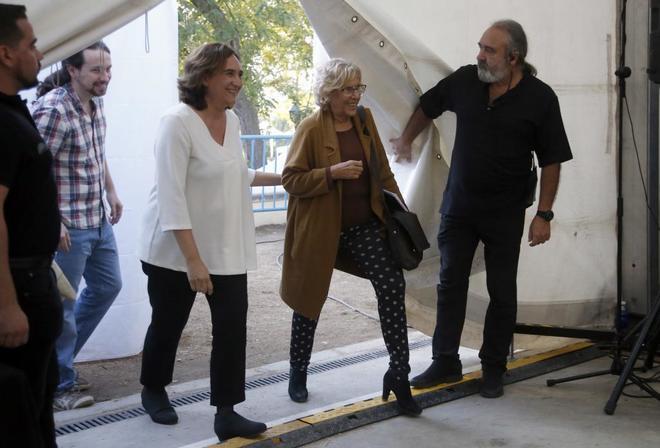 Las alcaldesas Manuela Carmena y Ada Colau y, detrás de ellas, Pablo Iglesias.