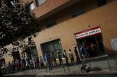 Una cola de personas que esperan a la entrada de una oficina de empleo...