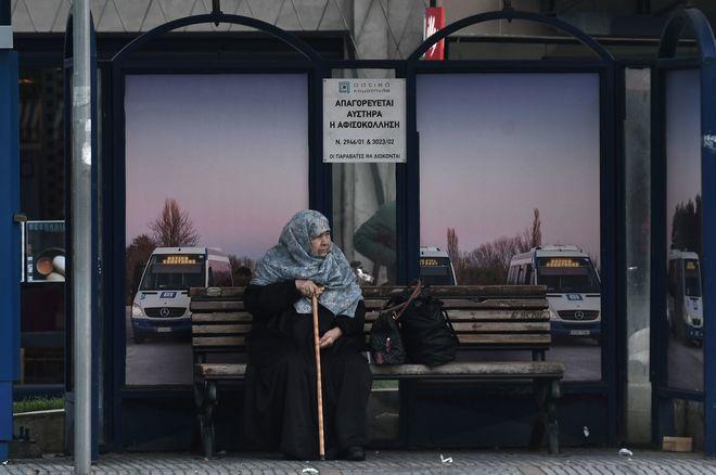Una mujer musulmana espera en una parada de autobús en Komotini (Grecia).