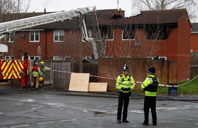 Miembros de la Policía frente a la casa incendiada.