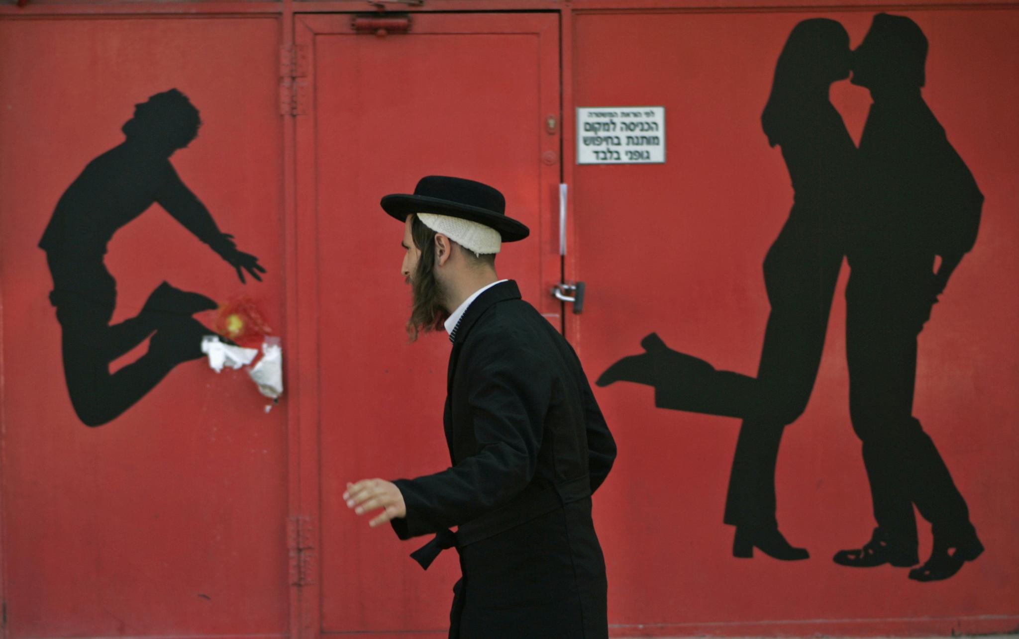 Un judío ultraortodoxo pasa por la entrada de un club de alterne en Tel Aviv.
