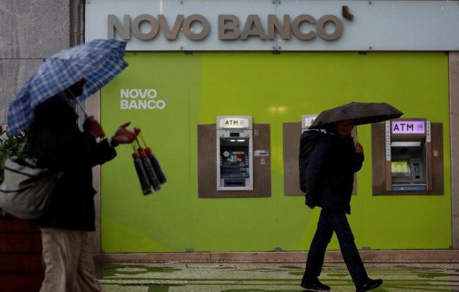 Varios hombres caminan delante de una oficina bancaria en Lisboa.