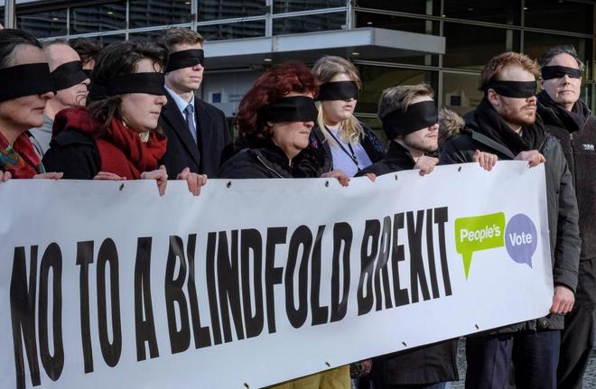 """Manifestantes con los ojos vendados sostienen una pancarta en la que se lee """"No a un Brexit a ciegas"""", ante la Comisión Europea, en Bruselas"""
