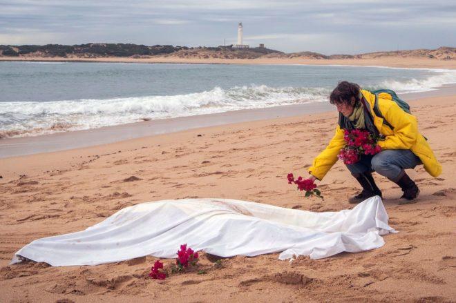 Una mujer deposita flores junto al cadáver de una persona en la playa de Caños de Meca, tras el naufragio de una patera en noviembre de 2018.