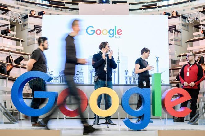 Empleados de Google delante del logotipo de la multinacional estadounidense.