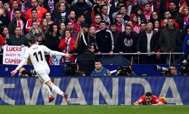 Bale, con Gimémez en el suelo, festeja el 1-3 ante la afición del Atlético.