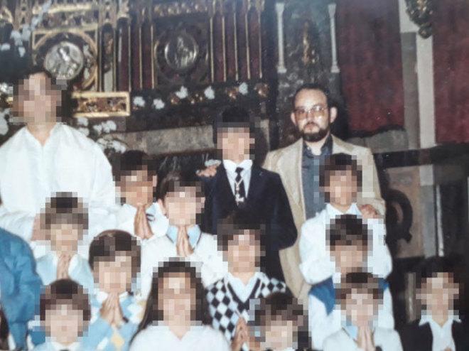 José Miguel San Martín, 'Don Chemi', con gafas y barba,  junto a un grupo de niños de Salesianos en su Primera Comunión, en una imagen de 1983 .