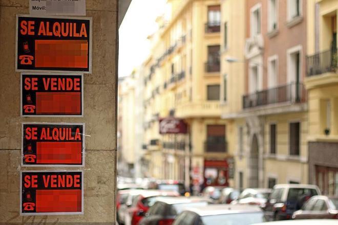 Carteles anunciando la venta de pisos en un edificio en Madrid.