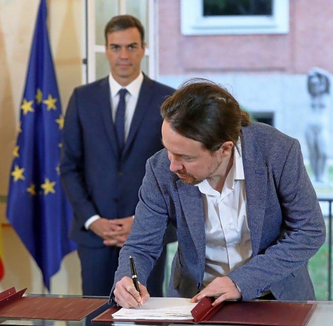 El secretario general de Podemos, Pablo Iglesias, firma los Presupuestos ante el presidente del Gobierno, Pedro Sánchez