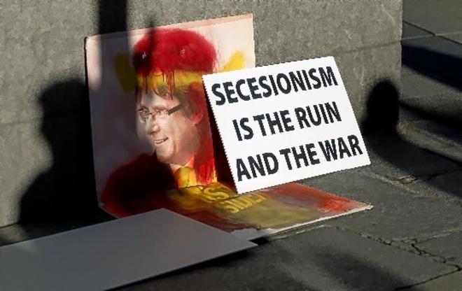 Un cartel favorable a Carles Puigdemont roto y pintado con los colores...