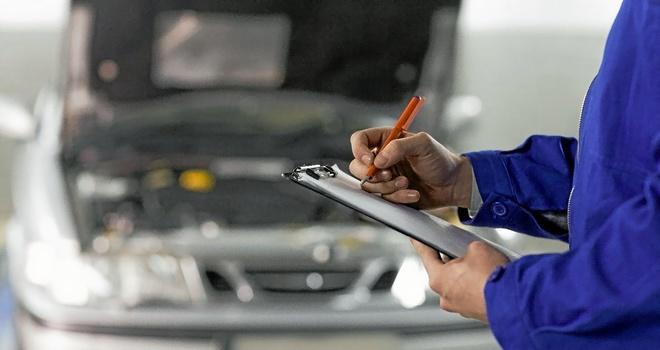 Un trabajador de un taller de reparación de vehículos toma notas delante de un coche.