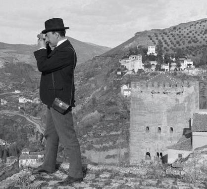 Imagen histórica de un turista fotografiando el Albayzín desde la alcazaba alhambreña.