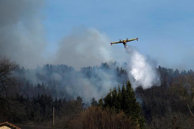Un hidroavión, durante las tareas de extinción de un incendio declarado en los montes próximos a la localidad cántabra de Penilla.
