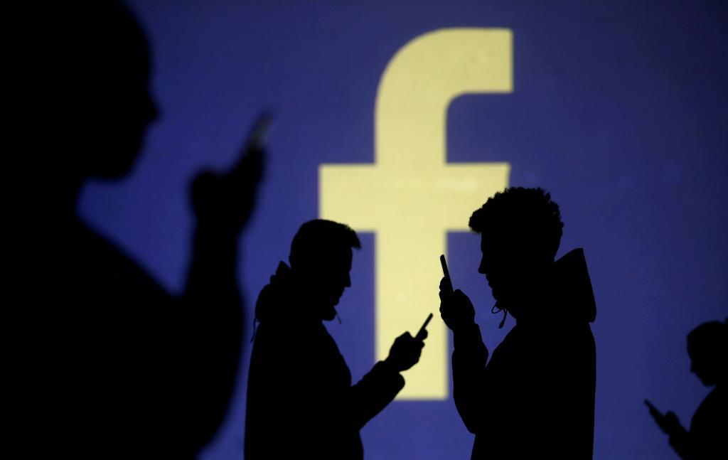 Siluetas humanas delante de un logo de Facebook.