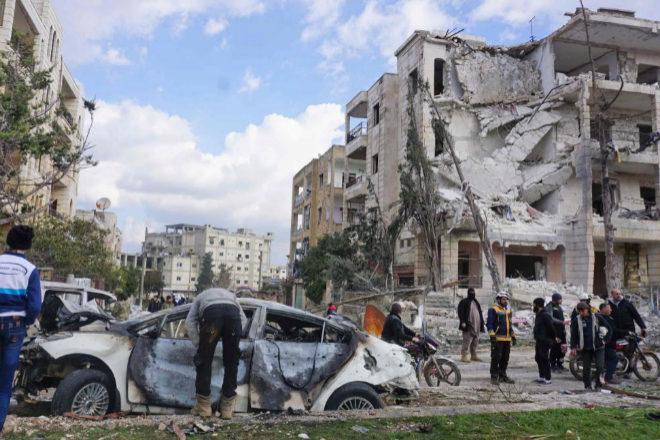 Varias personas observan los restos de uno de los cohces bomba que ha estallado en Idlib.